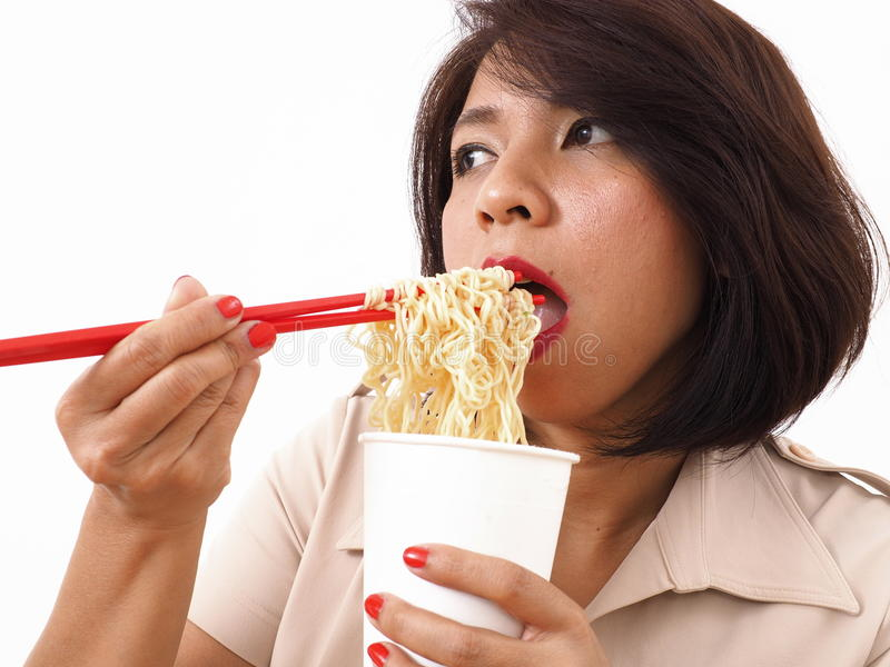 Busy Asian woman eating instant noodles. With red chopsticks royalty free stock photography