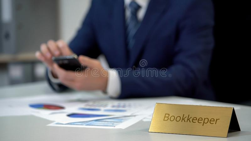 Busy bookkeeper typing message on smartphone, working on financial documents stock images