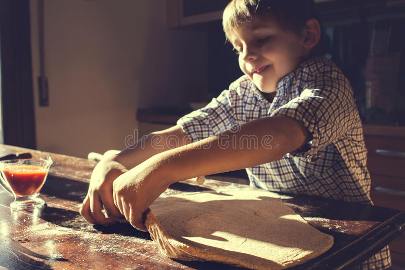 Busy boy trying to lift the pizza dough stock photo