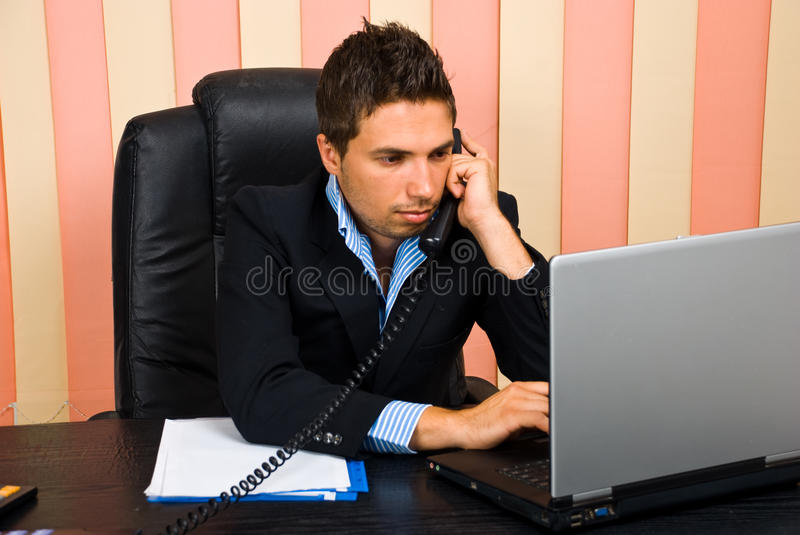 Busy business man in office. Sitting on chair at desktop talking by telephone and typing on laptop,check also royalty free stock images