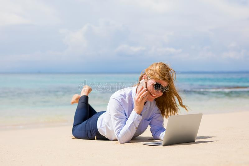 Busy woman enjoying working from the beach stock image