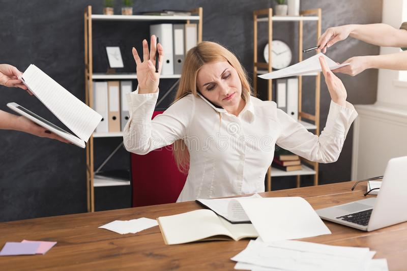 Busy woman in office gesturing stop to assistants. Busy business woman in office talking by phone and gesturing stop to her assistants, holding papers to sign stock images