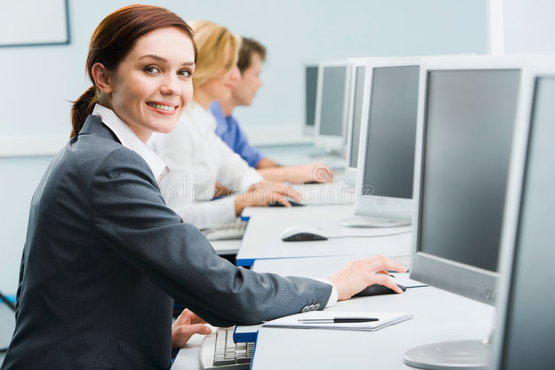 Busy business women. Portrait of busy woman sitting at the computer table and touching computer mouse on the background of businesspeople royalty free stock photos