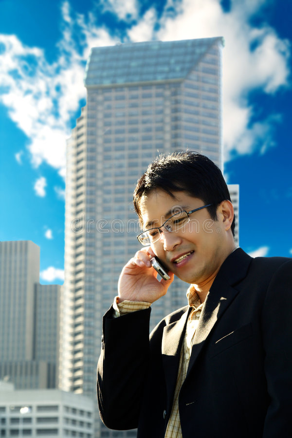 Busy businessman. A businessman talking on the phone at a business district stock image