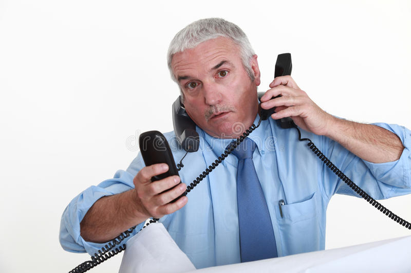A really busy businessman. A really busy businessman answering the phone royalty free stock image