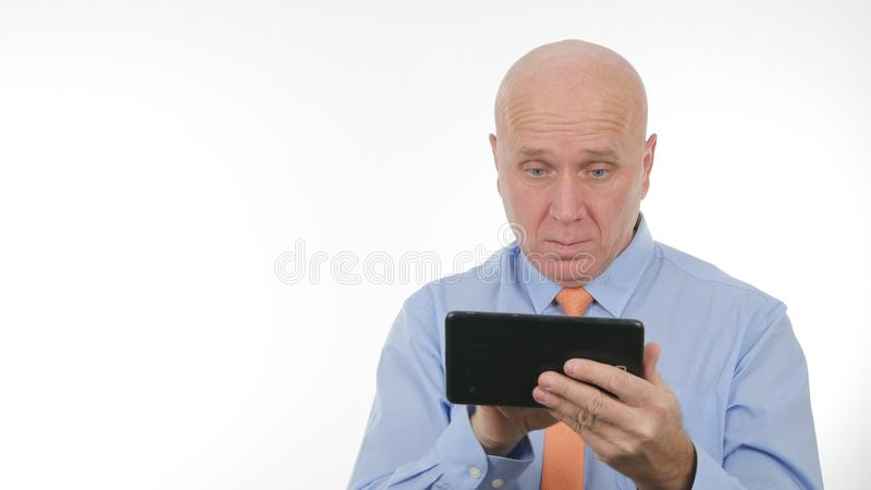 Busy Businessman Image Using a Tablet and Reading a Text royalty free stock photos