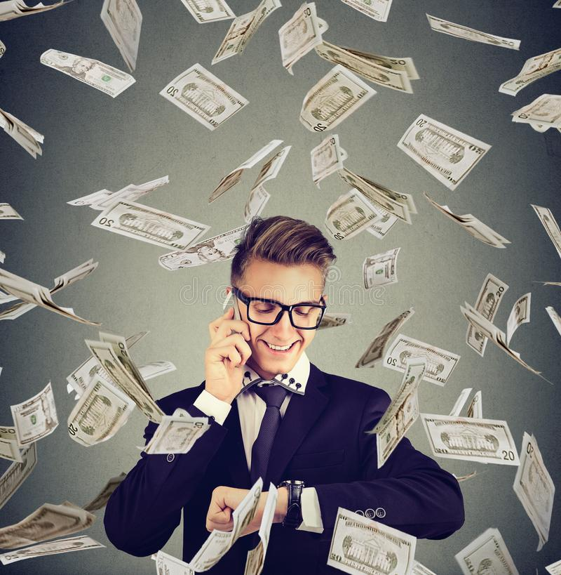 Busy businessman looking at wrist watch, talking on mobile phone under cash rain. Time is money concept royalty free stock photography