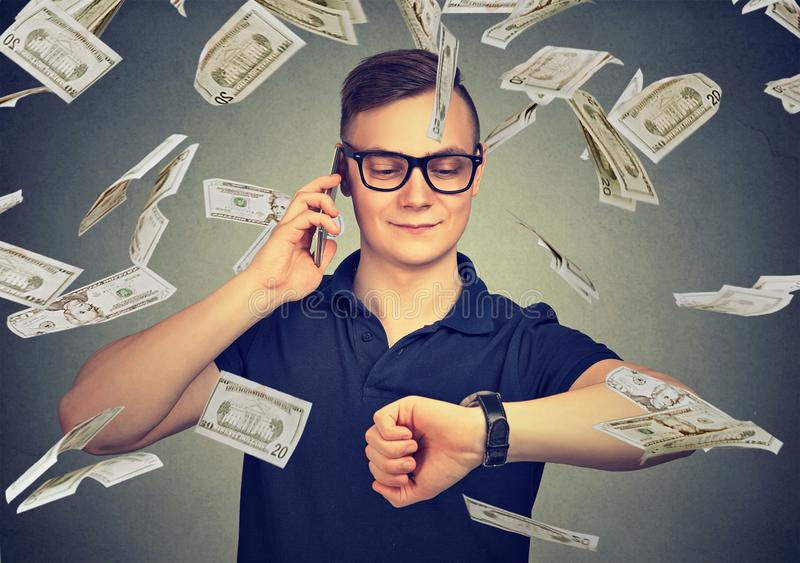 Busy businessman looking at wrist watch, talking on mobile phone under cash rain. Time is money concept. Busy business man looking at wrist watch, talking on royalty free stock photo