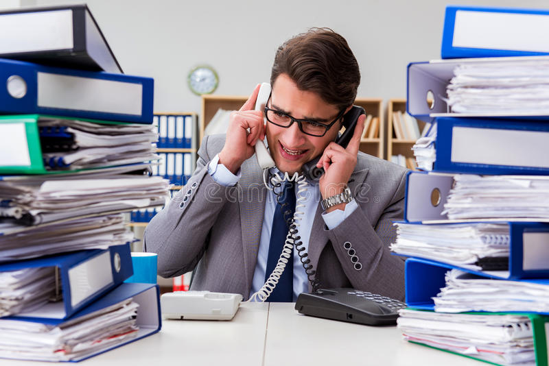 The busy businessman under stress due to excessive work royalty free stock photography