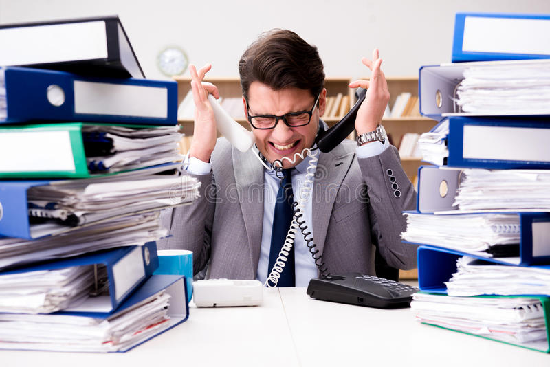 The busy businessman under stress due to excessive work. Busy businessman under stress due to excessive work stock images