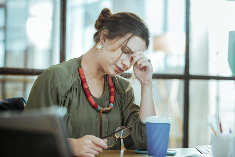 Busy businesswoman drinking some coffee having no energy. Having no energy. Busy businesswoman drinking some coffee having no energy and feeling tired stock photo