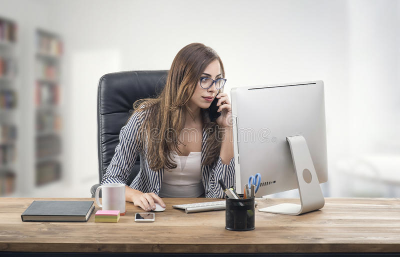 Busy Businesswoman in office and talking on mobile. Phone stock photo