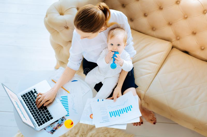 Busy businesswoman sitting with a funny baby. Tasty toy. Tired busy hardworking businesswoman not noticing her baby putting a toy into a mouth while sitting on royalty free stock images