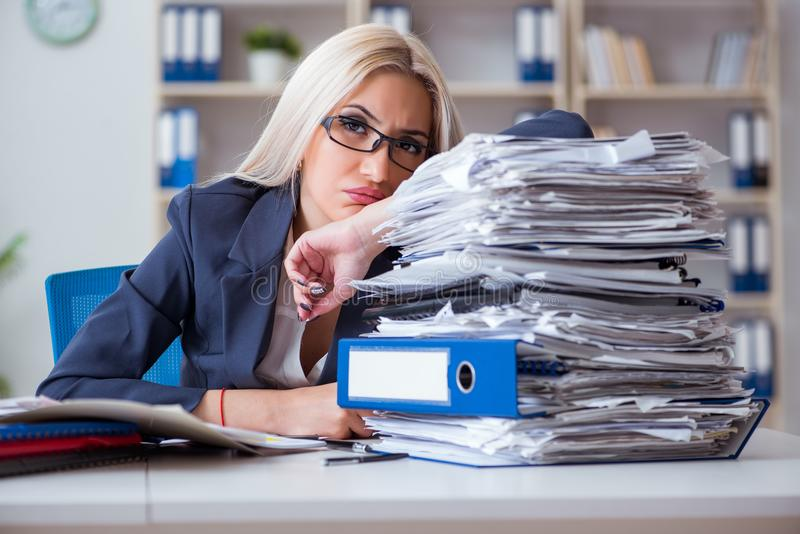 The busy businesswoman working in office at desk. Busy businesswoman working in office at desk royalty free stock image