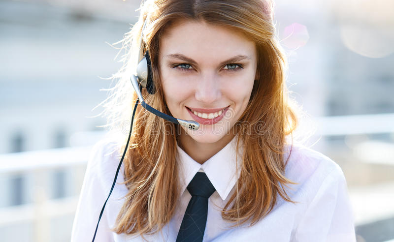 Busy call center agent speaking hands free. Smiling brunette girl in a shirt with a tie using handsfree stock photos