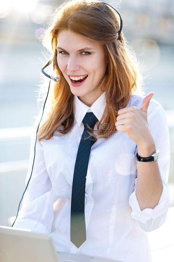 Busy Call Center Operator Girl shows It's OK!. Smiling brunette girl in a shirt with a tie raised his thumb up stock image
