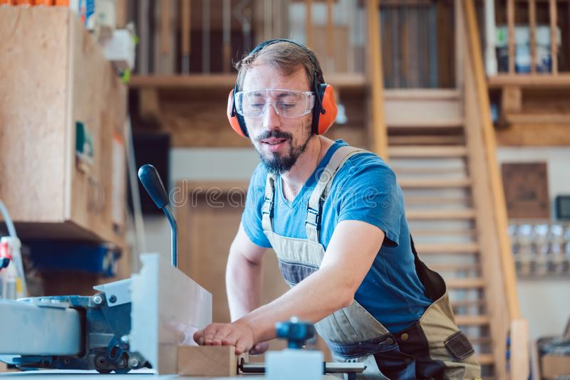 Busy carpenter at the circular cutter working with wood stock image