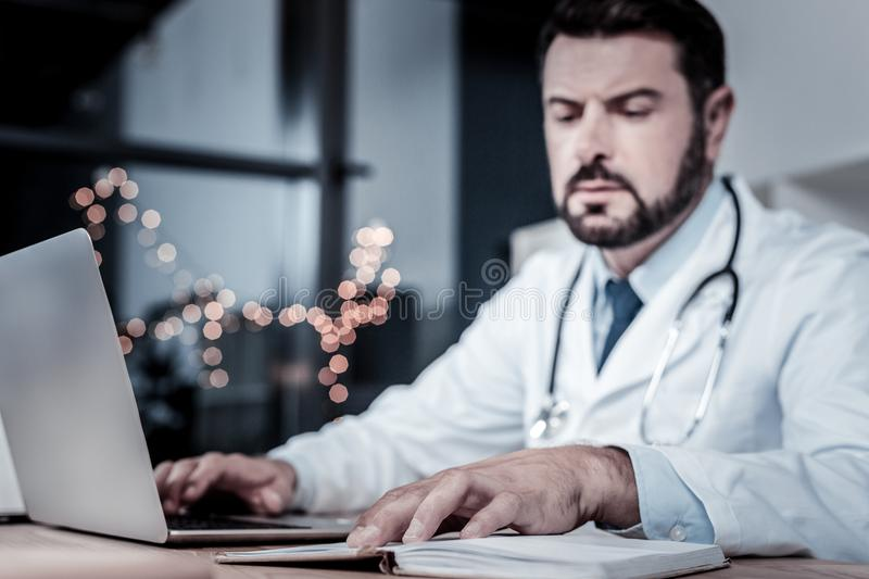 Busy confident medic using laptop and looking at his notebook. royalty free stock image