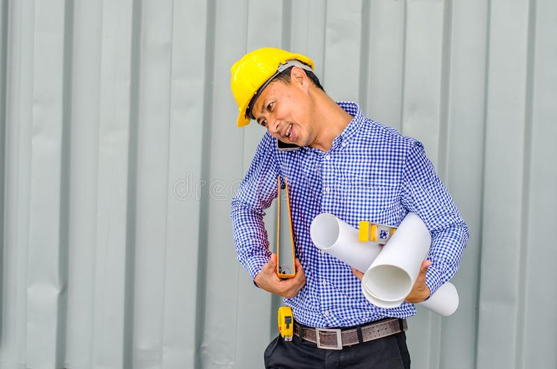 Busy construction engineer talking on phone while carrying blueprints stock photo