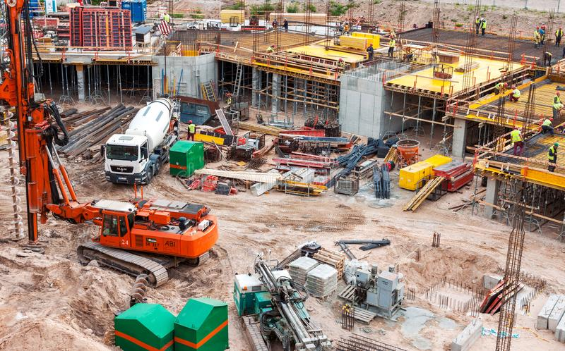 Busy construction site with machinery and workers stock image