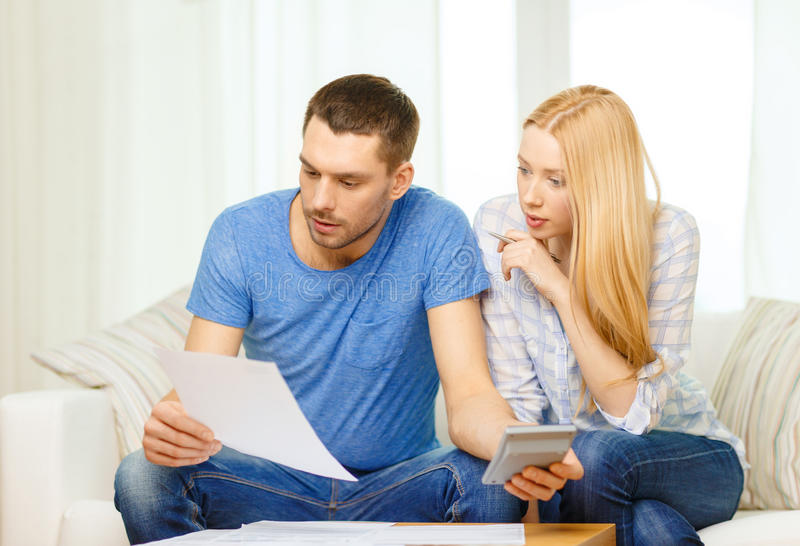 Busy couple with papers and calculator at home. Tax, finances, family, home and happiness concept - busy couple with papers and calculator at home stock photo