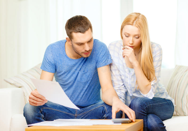 Busy couple with papers and calculator at home stock photo