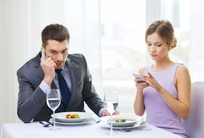 Busy couple with smartphones at restaurant stock photography