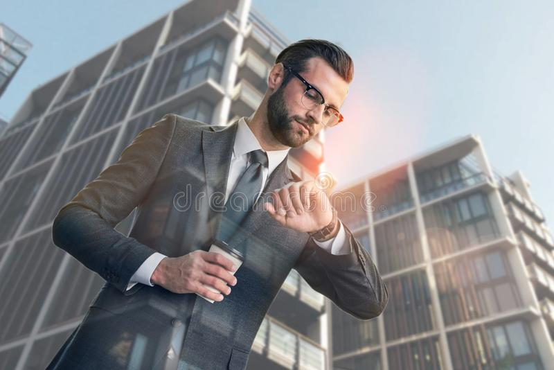Busy day. Handsome young businessman holding cup of coffee and looking at his watch while standing against of modern stock photography