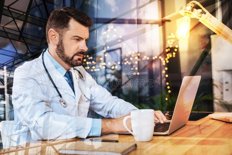 Clever young doctor working on his laptop and looking serious. Busy doctor. Calm attentive progressive doctor sitting in front of a modern laptop with a stock images