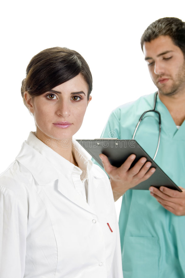 Download Busy Doctor Writing On Pad  With Nurse Stock Image - Image: 6548045