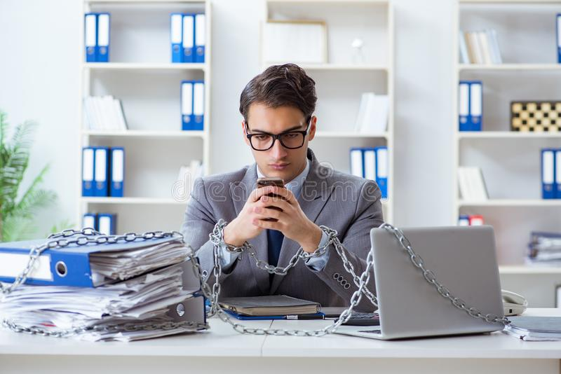 The busy employee chained to his office desk. Busy employee chained to his office desk royalty free stock photography