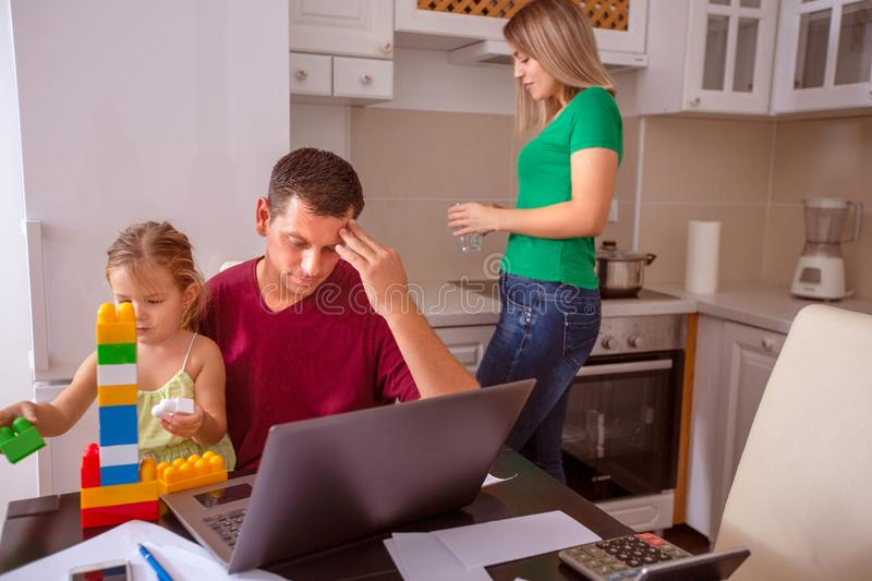 Busy family - Man working with computer while looking after his daughter royalty free stock image