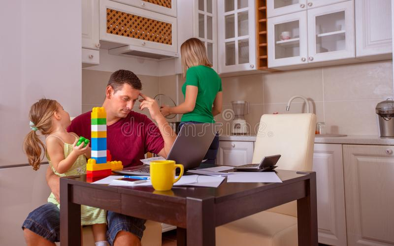 Busy Family Home with Father Working as Mother Prepares Meal stock photo