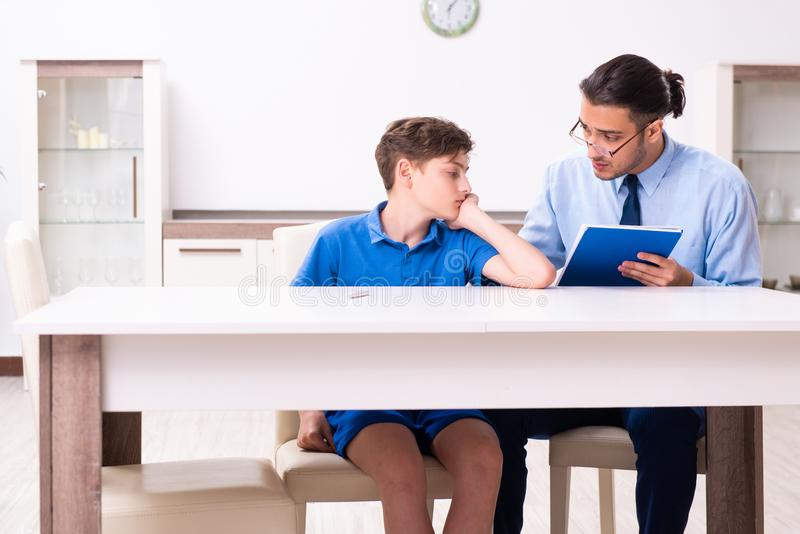 Busy father helping his son to prepare for exam. The busy father helping his son to prepare for exam royalty free stock image