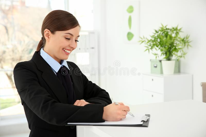 Busy female receptionist at workplace stock image