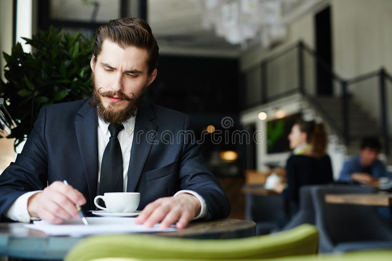 Busy financier. Serious employer reading resumes of applicants in cafe by cup of tea stock photos