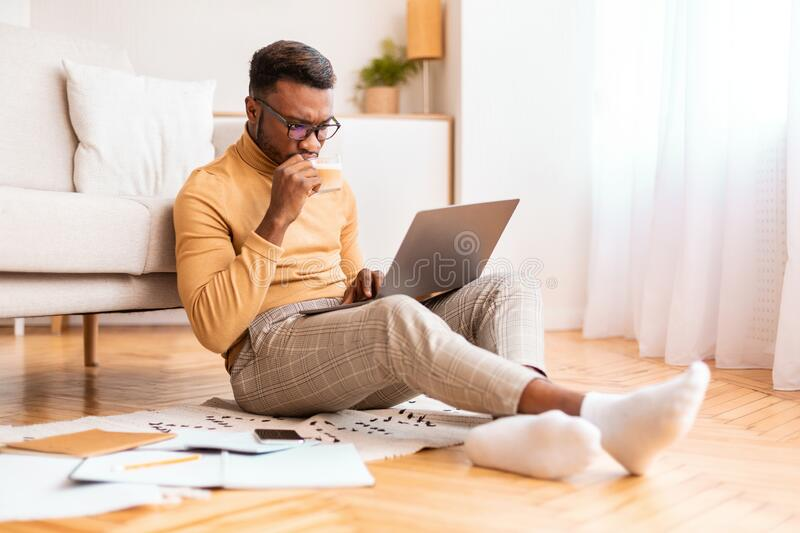Busy Freelancer Guy Using Laptop Working Sitting On Floor Indoor stock photos