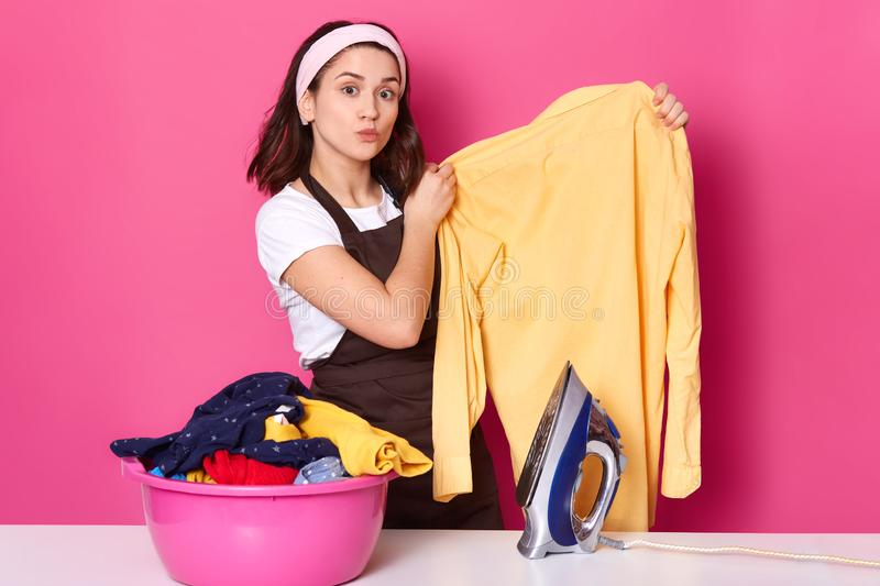 Busy hard working black haired housewife doing ironing after laundry, holding ironed yellow shirt, being busy with household. Chores, looks busy and attentive royalty free stock photos