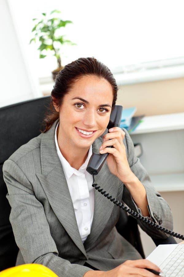 Busy hispanic female architect talking on phone stock photo