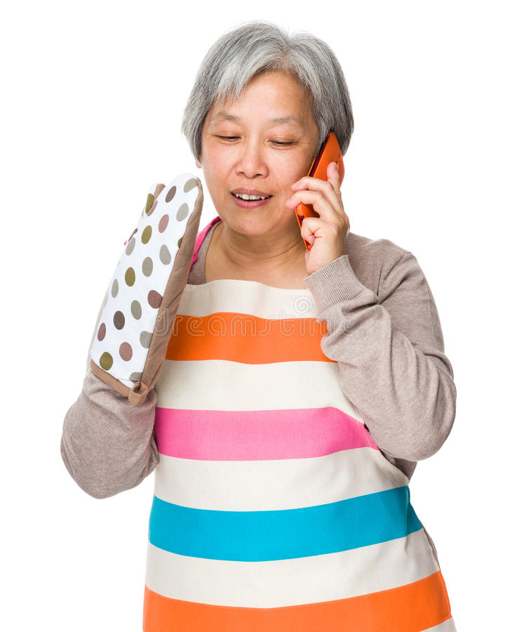 Busy housewife talk to mobile phone. Isolated on white background royalty free stock images