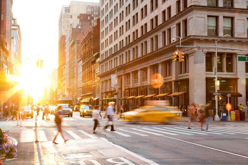 Busy intersection of 23rd Street and 5th Avenue in Manhattan is crowded with people and traffic as the sun sets in the background. New York City June, 2018 stock photography