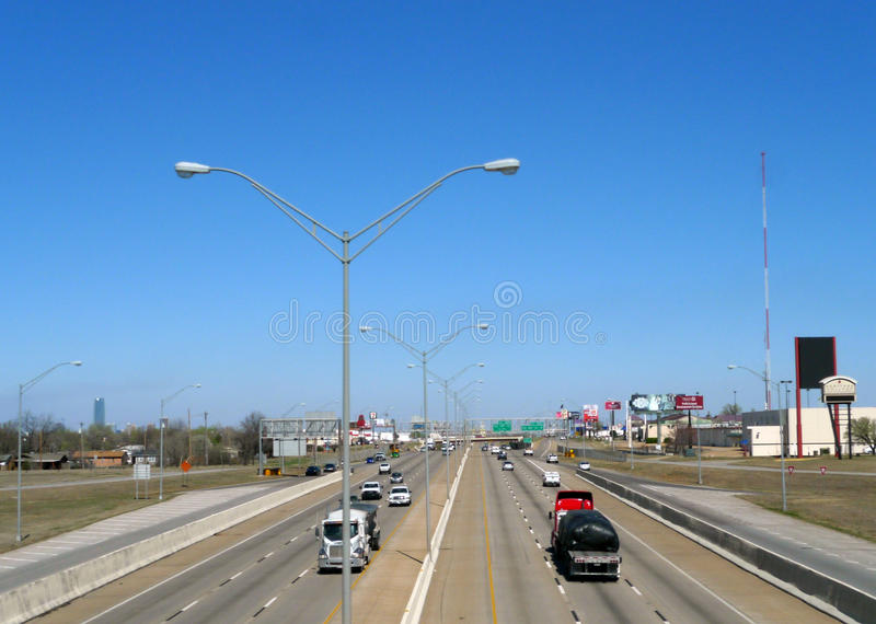 Busy interstate system in Oklahoma City, Oklahoma. Daytime traffic and industry along the interstate in mid city. Photo from above with busses, trucks, cars and stock photos