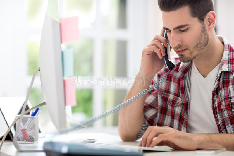 Busy man in office. Sitting at desk, back view stock photography