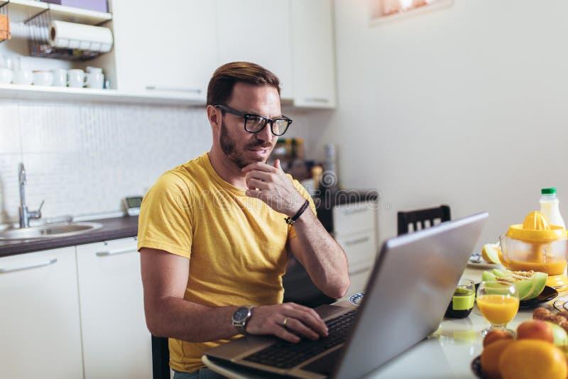 Man working at home, using laptop while having breakfast. Busy man working at home, using laptop while having breakfast royalty free stock photography