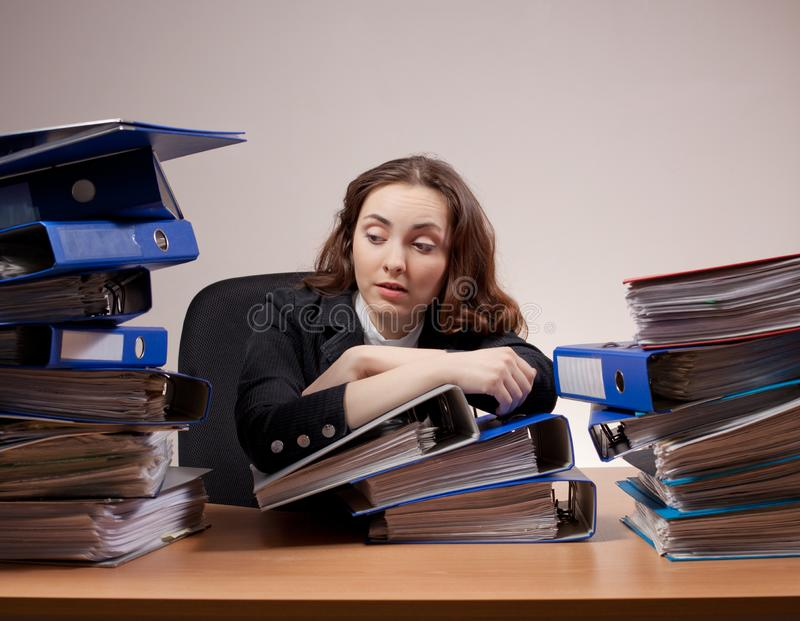 Busy manager. Stressed businesswoman with stack of folders and d stock image