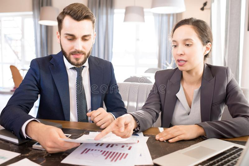 Busy managers analyzing data report. Serious concentrated young multiethnic business people analyzing data report and brainstorming about company development stock photos