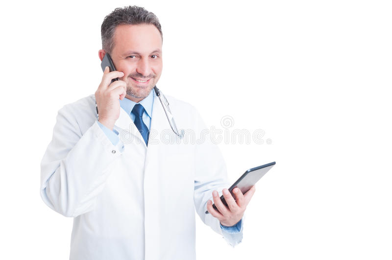 Busy medic or doctor multitasking with phone and tablet. Isolated on white background royalty free stock photography