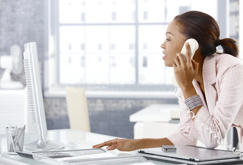 Busy office girl on phone stock image