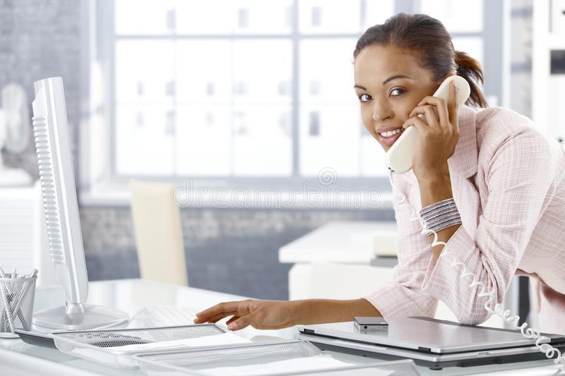 Busy office girl on phone. Busy office girl speaking on landline phone at desk, smiling at camera stock images