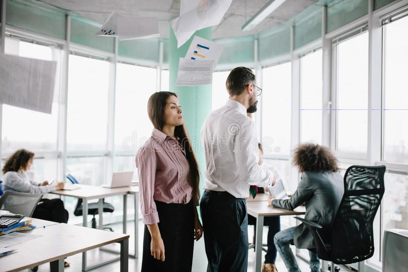 Busy office weekdays during project. Man and women standing together under flying documents. Angry because of mistakes stock image